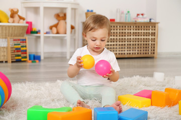 Cute baby girl playing with colorful balls on a carpet