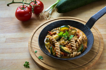 Vegetables with whole grain pasta in a rustic pan on a wooden kitchen board