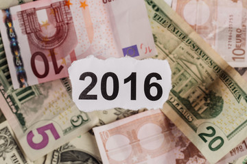Focus on the words 2016 on piece of torn white paper with USD.