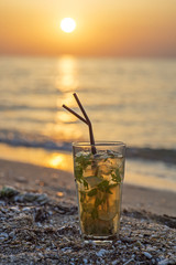 Glass with mojito cocktail on beach