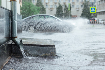 Rain water flowing from metal drainpipe during a flood. splashes of cars background. concept  protection against heavy downpours.