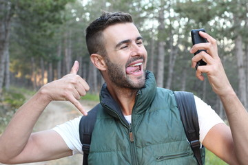 Closeup on person using smart phone and showing thumb up finger while making a video call or taking a selfie