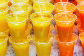 rows of plastic cups with fruit juices