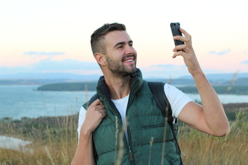 Just look! I am here! Handsome young man carrying backpack and taking a picture of himself and pointing to the gorgeous view