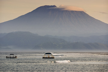 Mt. Agung from Nusa Lembongan. Sunrise view of the volcano known as Gunung Agung as seen from the small island off the coast of Bali known as Nusa Lembongan. This island has seaweed farms and surfing.