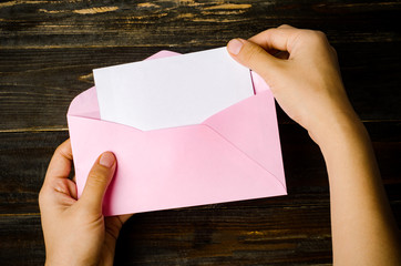 Pink envelope and blank white card holding by hand