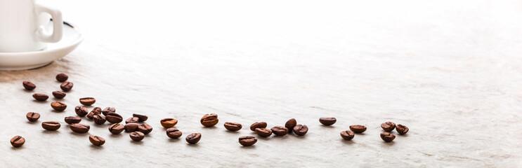 Kaffeebohnen und Kaffeetasse auf heller Steinplatte, Panorama, Makro