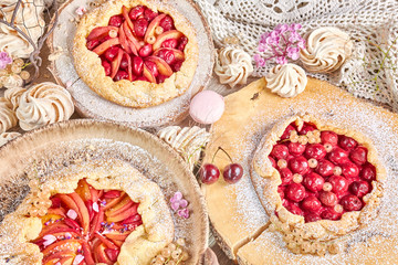 Rustic fruit tarts and meringues, homemade pastry, pastel colors.