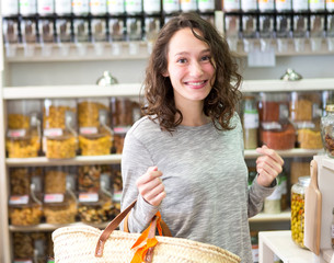 View of a Young attractive woman shooping looses spices at the grocery