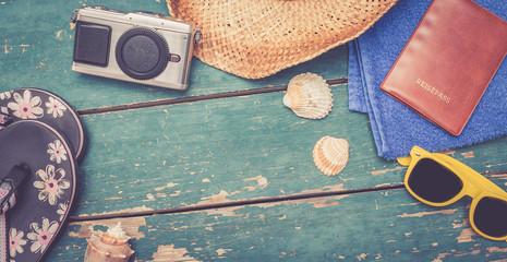 Strohhut, Flipflops, Reisepass, Fotoapparat und Muscheln auf Holzuntergrund, widescreen