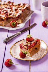 Summer light cake with strawberries on a lilac wooden background with fresh berries