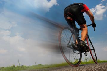 cyclist riding fast on the asphalt road
