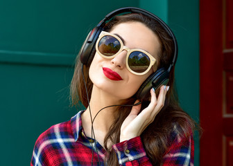 Beautiful smiling woman with headphones listens to music. Fashio
