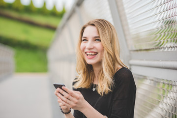 Portrait of young beautiful caucasian blonde hair woman outdoor using smart phone hand hold smiling - social network, communication, technology concept