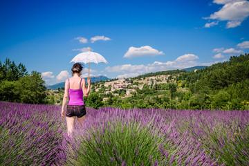 Femme et son ombrelle dans un champ de lavandes en Provence