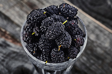 Ripe mulberries in wine glass