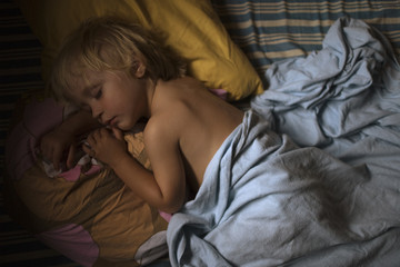 A boy sleeping in a bed