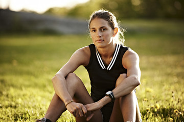Young female runner relaxing, Sweden.