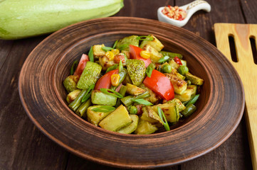 Dietary vegetarian salad with grilled zucchini, fresh tomatoes, sweet corn and herbs in a clay bowl on dark wooden background.