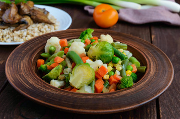 Steamed summer vegetables (broccoli, sweet corn, asparagus, brussels sprouts, carrots) in a clay bowl. Light vegan diet garnish.