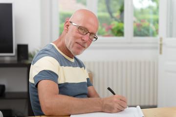 senior man writing on a notebook