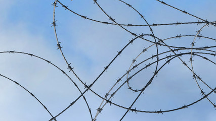 Barbwire over blue sky background