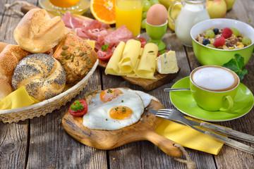 Gedeckter, rustikaler Frühstückstisch im Sonnenlicht mit zwei Spiegeleiern und weiterer reichlicher  Auswahl - Outside served breakfast with fried eggs a wide selection of other foods