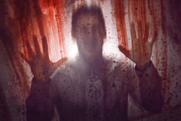 Mann hinter blutbefleckter Fensterscheibe