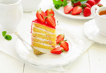 A piece of sponge cake with strawberries and cream.