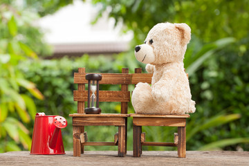Teddy bears sitting on a wooden chair backyard.