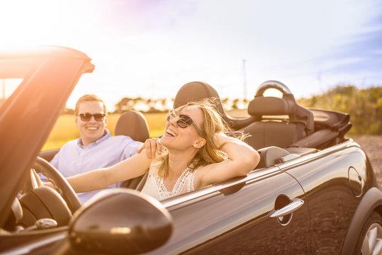 Mit dem Cabrio unterwegs - Verliebtes Paar im Cabrio lacht und ist glücklich