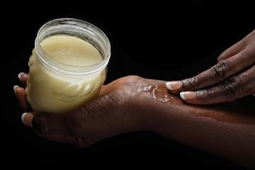 femme noire africaine mettant beurre de karité sur sa peau