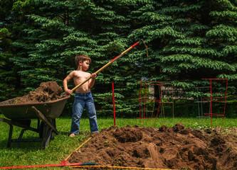Boy hoeing soil in garden