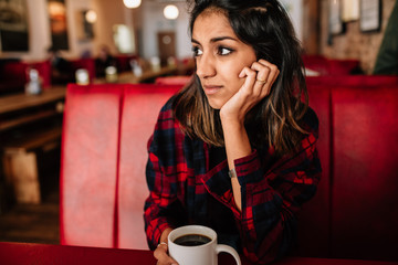 Thoughtful young woman having coffee at cafeteria