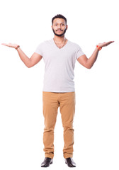 Serious and concentrated latino man with beard spreads his arms. He is trying to compare something. Full length portrait. Isolated on white background.