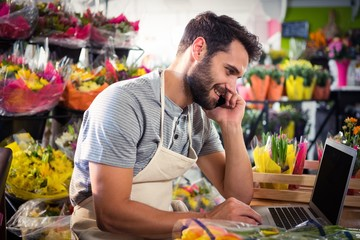 Male florist talking on mobile phone while using laptop
