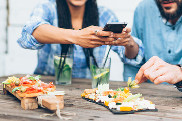 Young couple sitting in the restaurant and taking pictures of the food with mobile phone