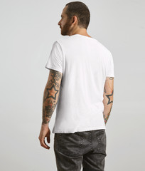 Attractive brutal tattooed bearded guy poses backside in black jeans and blank white t-shirt from premium thin summer cotton, isolated on white mockup