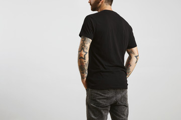 Brutal attractive bearded biker man with tattooed hands poses backside in black blank t-shirt from premium thin cotton, isolated on white mockup