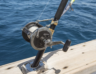 Closeup of fishing rod reel on side of boat