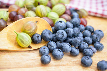 Fresh blueberry and gooseberry on the wooden table - food picture