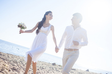 Just married happy couple running on a sandy beach