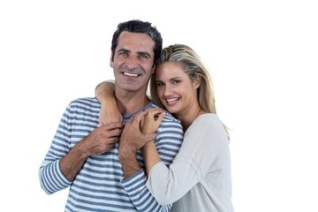 Mid adult romantic couple embracing against white background