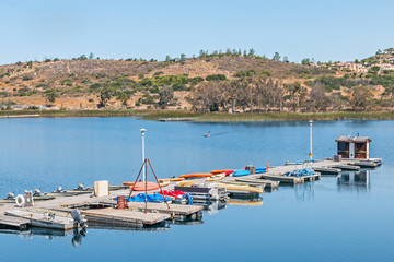 Small boat rental dock by rural lake, calm blue water and hills