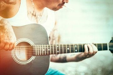 Hipster  with tattoos playing guitar. Lens flare added.
