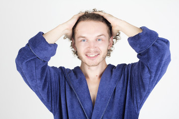 Happy handsome man in bathrobe touching his hair. Man smiling with teeth.