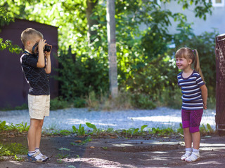 Little boy taking the picture of a litthe girl on sunny summer d