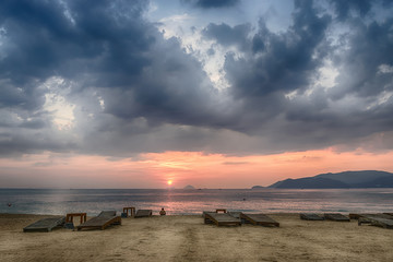 Vietnam, Nha Trang, Sandy beach, empty sunbeds, the calm sea, the sunrise, a lone man is looking into the distance