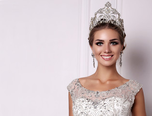woman with dark hair in luxurious wedding dress and precious crown
