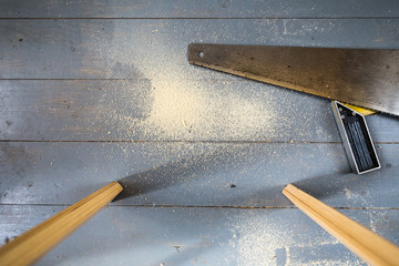 hand saw and sawdust on the floor during the repair
